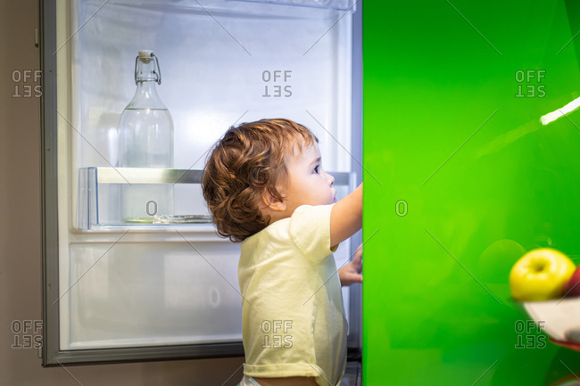 Side view of cute little child standing on stool and taking food from open refrigerator in cozy kitchen at home