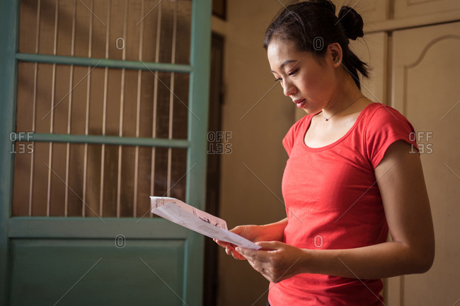 Ethnic female in red t shirt examining manual paper while standing in cozy room at home