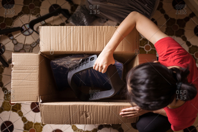 Top view of anonymous female taking parts of chair from carton box before assembling furniture at home