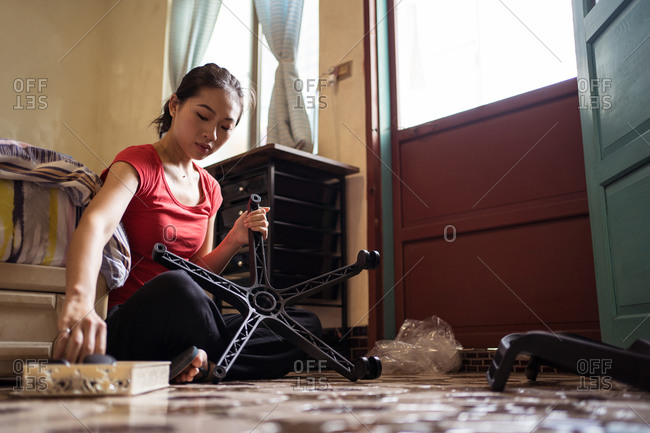 Side view of ethnic Asian female screwing wheels to chair base while sitting cross legged on floor near bed and assembling furniture in cozy bedroom at home