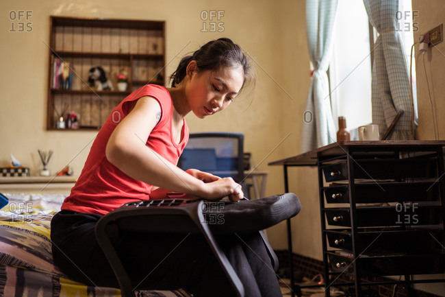 Low angle of ethnic lady sitting on bed and checking soft seat with handles while assembling chair at home