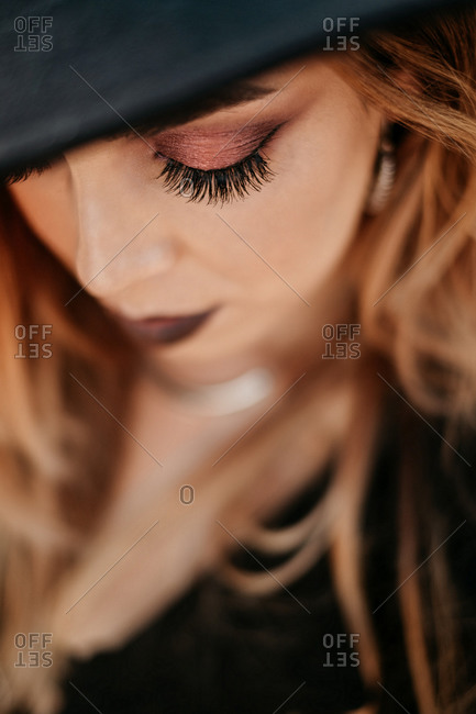 Trendy lady touching hat and looking down