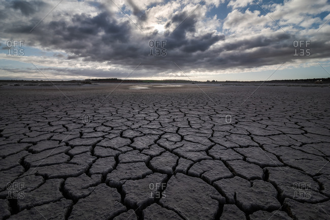 From above of drought cracked lifeless ground under colorful cloudy sky