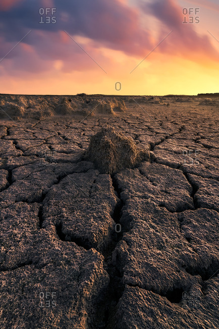 From above of drought cracked lifeless ground under colorful cloudy sky at sunset time