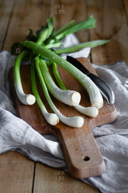 Bunch of ripe scallions placed on wooden cutting board and cloth napkin on rustic table in kitchen