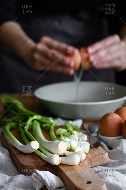 Cropped woman hands breaking eggs in a bowl with bunch of fresh scallions and mushrooms placed on cutting board near poppy seeds