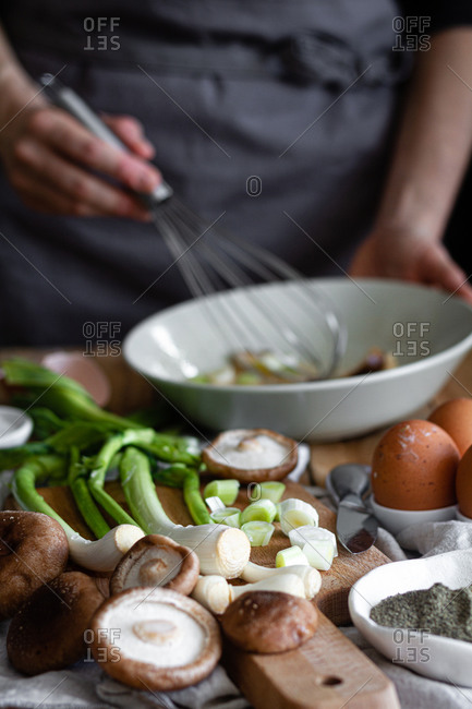 Bunch of fresh scallions and mushrooms placed on cutting board near eggs and poppy seeds against crop housewife mixing ingredients in bowl