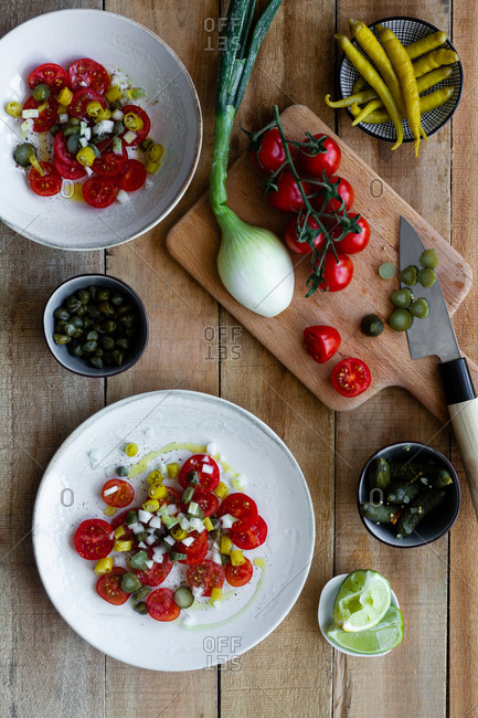 Top view of plates with salad made of fresh cherry tomatoes and pickled cucumbers with hot pepper and scallion and placed on wooden table near squeezed lime