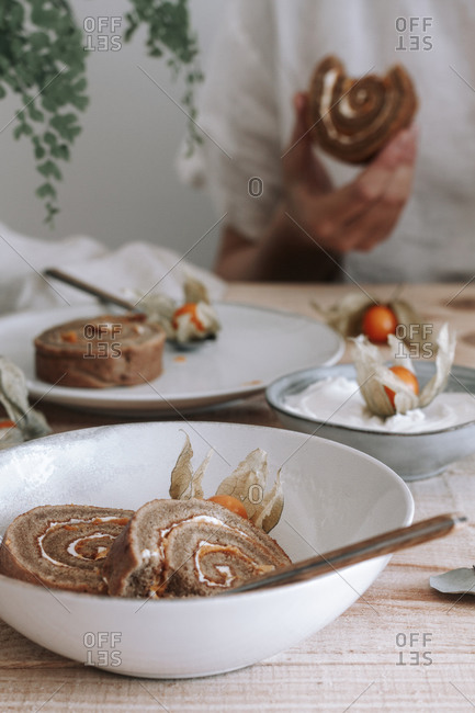 From above of sliced delicious homemade sweet roll cake with whipped cream and Physalis dried flowers served on plate on wooden table with ingredients