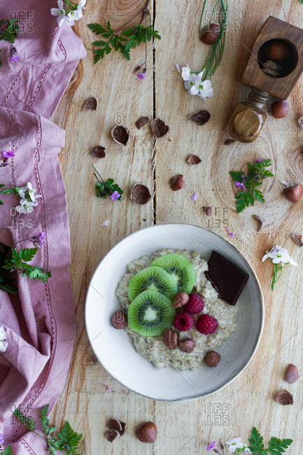 Top view of slices of fresh kiwi and raspberries placed near chocolate and hazelnuts in bowl of healthy porridge on wooden table near lilac cloth