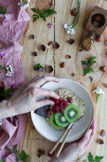 From above cropped unrecognizable person adding raspberries into a healthy porridge bowl with sliced fresh kiwi, slice of chocolate and hazelnuts on wooden table with flowers