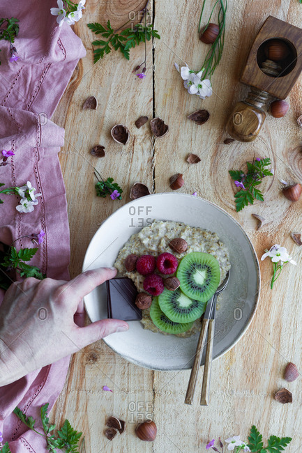 Top view of cropped unrecognizable person adding slice of chocolate to a healthy porridge bowl with sliced fresh kiwi, raspberries and hazelnuts on wooden table with flowers