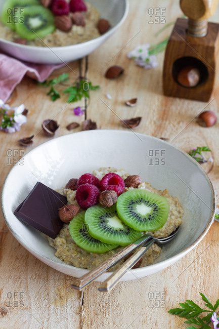 From above slices of fresh kiwi and raspberries placed near chocolate and hazelnuts in bowl of healthy porridge on wooden table near lilac cloth