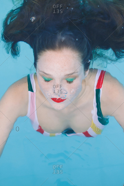 close-up of a brunette girl with hair submerged in the pool with her eyes closed