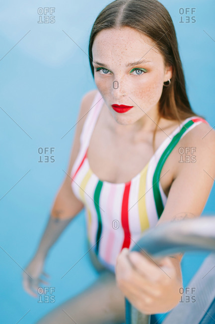 Close-up of a brunette girl with long hair on a stairs in the pool