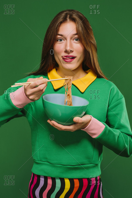 Positive young female in green shirt looking at camera grimacing sticking tongue out while eating yummy instant noodles with chopsticks on green background