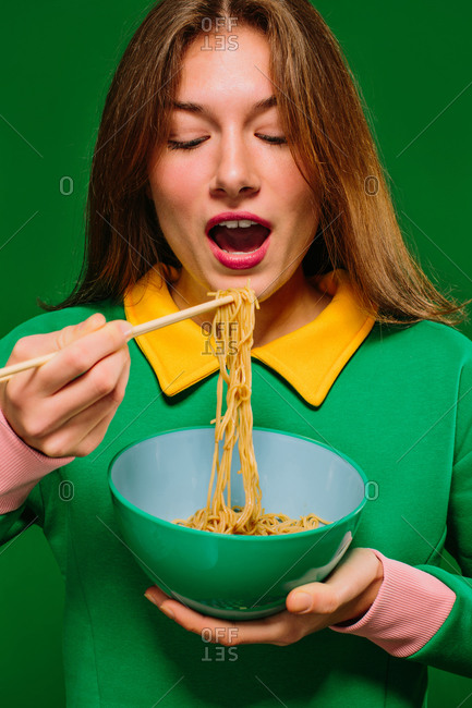 Positive young female in green shirt with closed eyes while opening mouth to eat yummy instant noodles with chopsticks on green background
