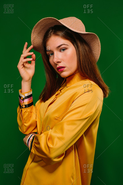 Side view of trendy confident millennial female in colorful clothes and hat looking at camera against green background