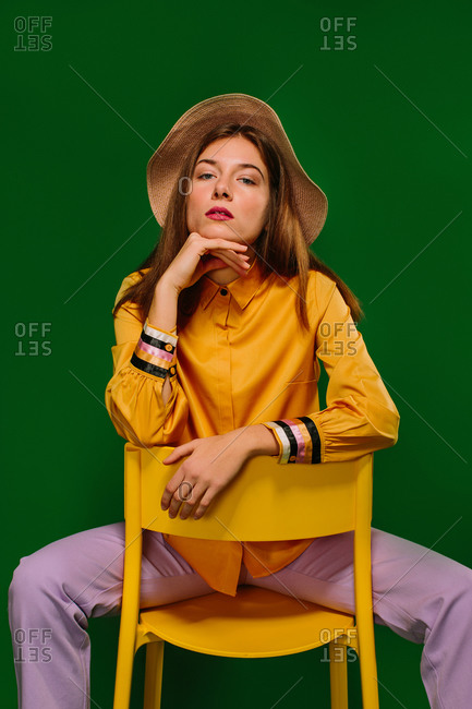 Trendy confident millennial female in colorful clothes and hat sitting on stool and looking at camera against green background