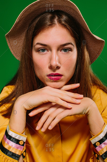 Trendy confident millennial female in colorful clothes and hat looking at camera leaning on hand against green background