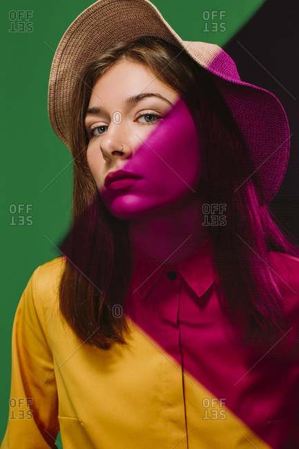 Young female model in stylish hat with red shadow on face and shoulder looking at camera against green background