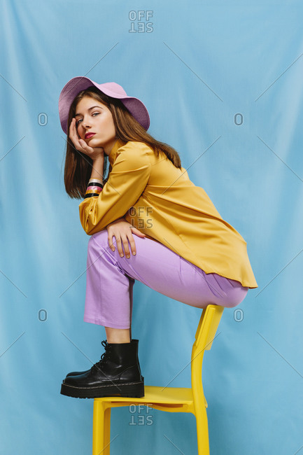 Side view of trendy confident millennial female in colorful clothes and hat sitting on stool and looking at camera against blue background