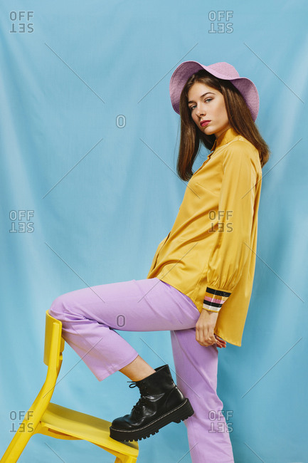 Side view of trendy young confident female in stylish colorful wear and hat looking at camera while standing steeping foot on yellow chair against blue background
