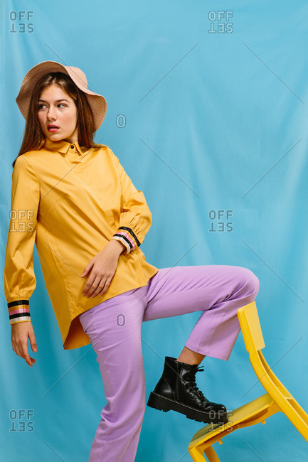 Side view of trendy young confident female in stylish colorful wear and hat looking away while standing steeping foot on yellow chair against blue background