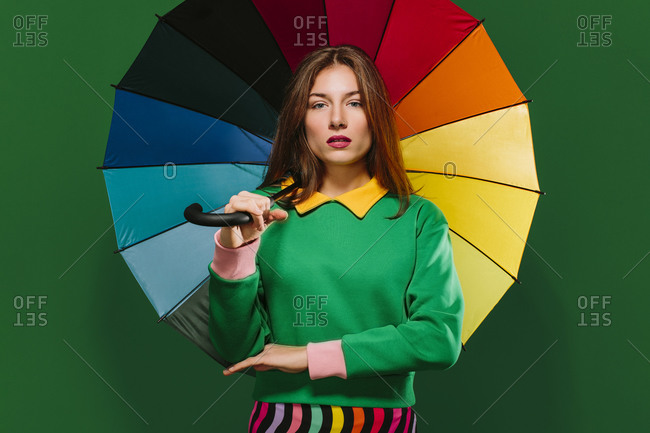 Young unemotional female model in colorful outfit holding multicolored umbrella and looking at camera while standing against green background