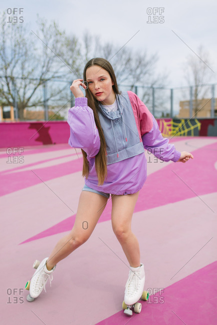Stylish teenager skating on playground