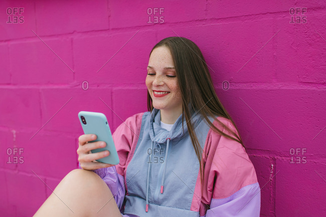 Happy teen female in trendy colorful jacket browsing mobile phone while sitting near pink stone wall on street