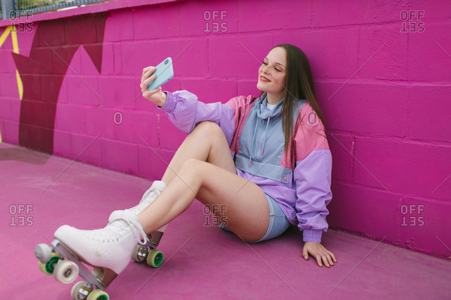 Cheerful young woman using smartphone on street