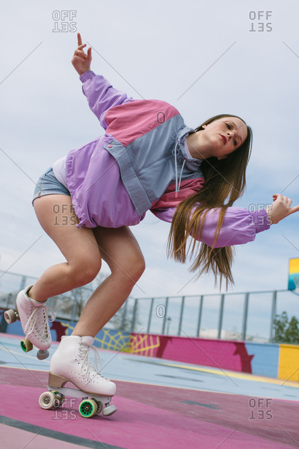 Low angle of modern teen female in bright trendy clothes running on roller skates on colorful playground in city