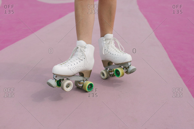 From above of crop anonymous female on vintage white roller skates standing on pink sports ground