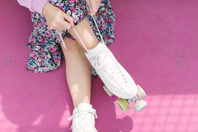 Woman tying laces on roller skates
