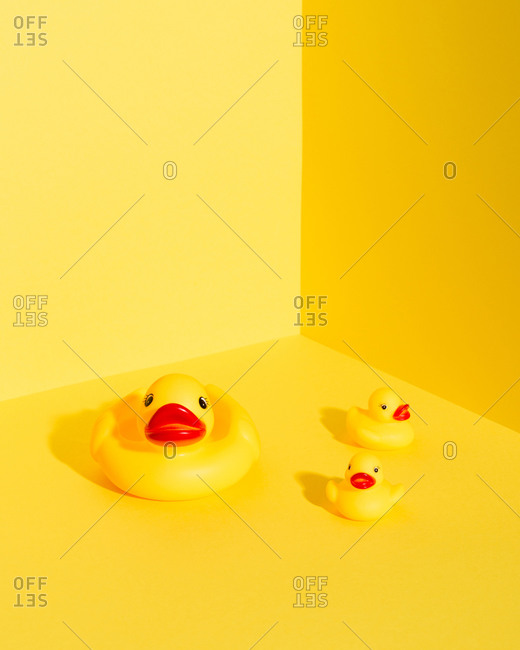 From above set of cute rubber ducklings and duck mom toys placed on bright yellow background