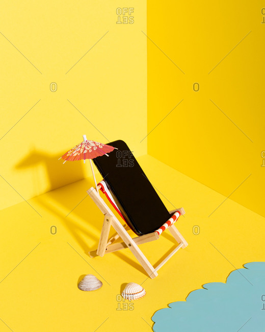 From above composition of miniature deckchair with parasol and mobile phone placed near blue sea against yellow background