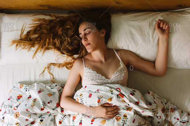 From above of young serene female with long wavy hair wearing lace bra sleeping in cozy bed with white sheets and ornamental blanket