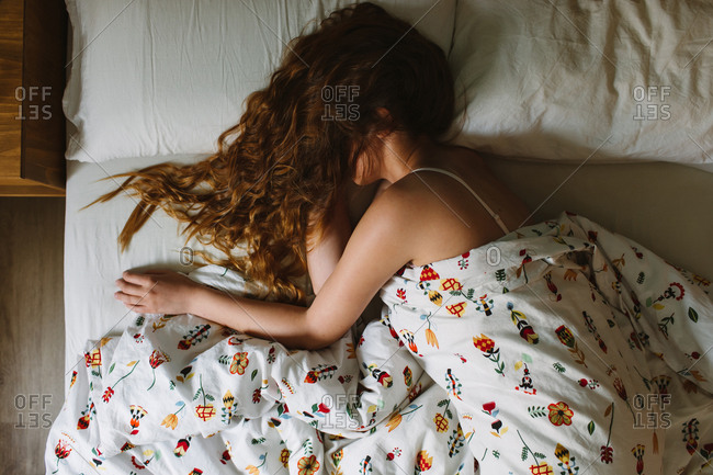 From above side view of unrecognizable serene female with long wavy hair over the face wearing lace bra sleeping in cozy bed with white sheets and ornamental blanket