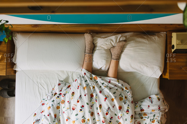 From above of crop anonymous female wearing socks lying in bed covered with blanket with legs on pillows