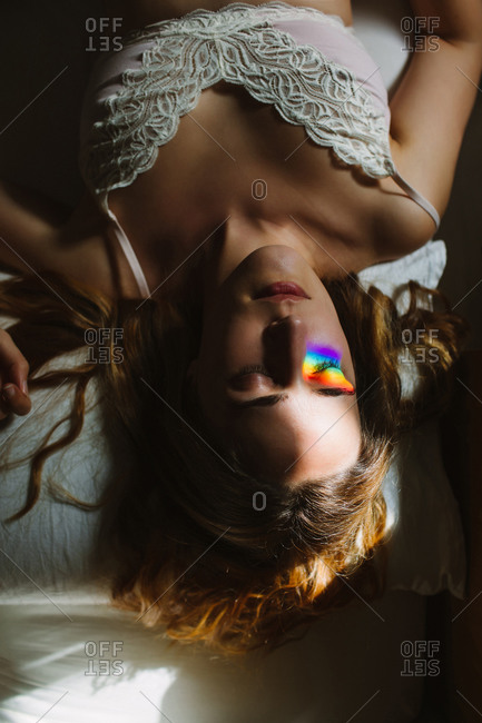 From above of young sensual female in white lace bra with colorful rainbow blink on face with closed eyes sleeping in bed in morning