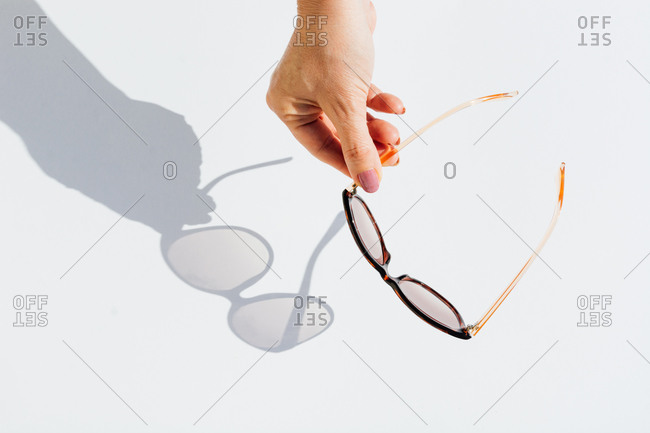 From above cropped anonymous female hands holding trendy sunglasses with brown lens and frame over white background with shadow