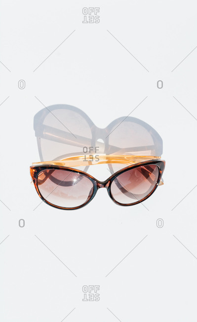 From above of trendy elegant female sunglasses with brown frame placed on white background in light studio