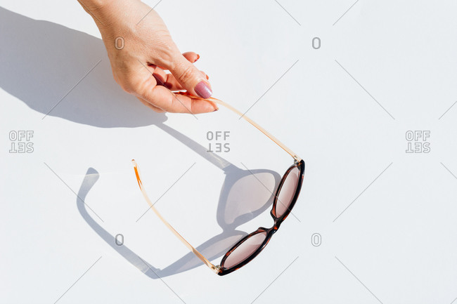 From above top view of cropped anonymous female hands holding trendy sunglasses with brown lens and frame over white background with shadow