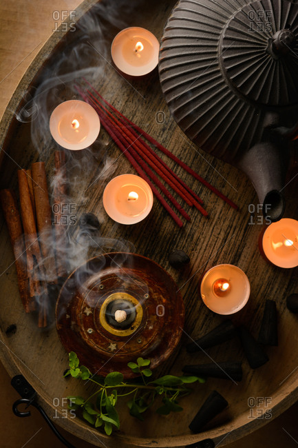 Composition of burning incense cone and tea candles on wooden tray with oriental teapot prepared for relaxation and meditation