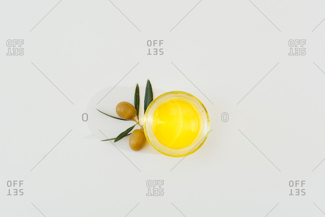 From above of natural olive oil in glass jar placed on white table with green olive tree branches