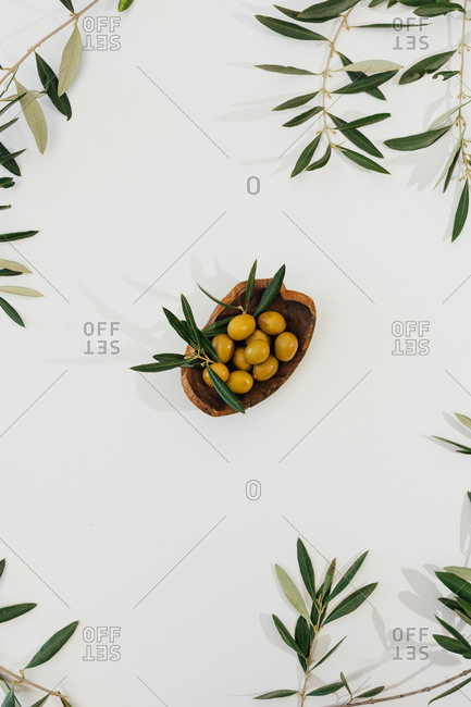 Top view composition of fresh tasty green olives in wooden bowl framed by olive tree branches on white background