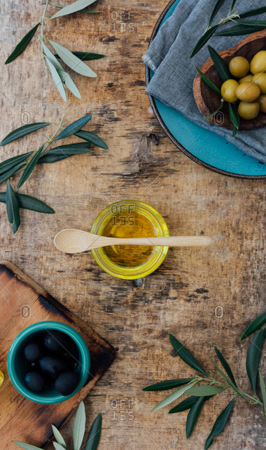 From above of glass jar with organic olive oil with wooden spoon placed on shabby gray table near fresh green olives and tree branches