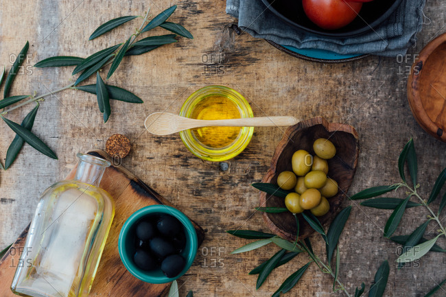 From above of glass jar with organic olive oil with wooden spoon placed on shabby gray table with fresh tomatoes green and black olives near tree branches