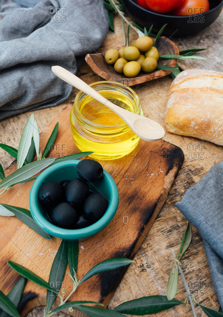 From above olive oil in a glass jar ready to prepare delicious salad with ripe red tomatoes at wooden rustic table